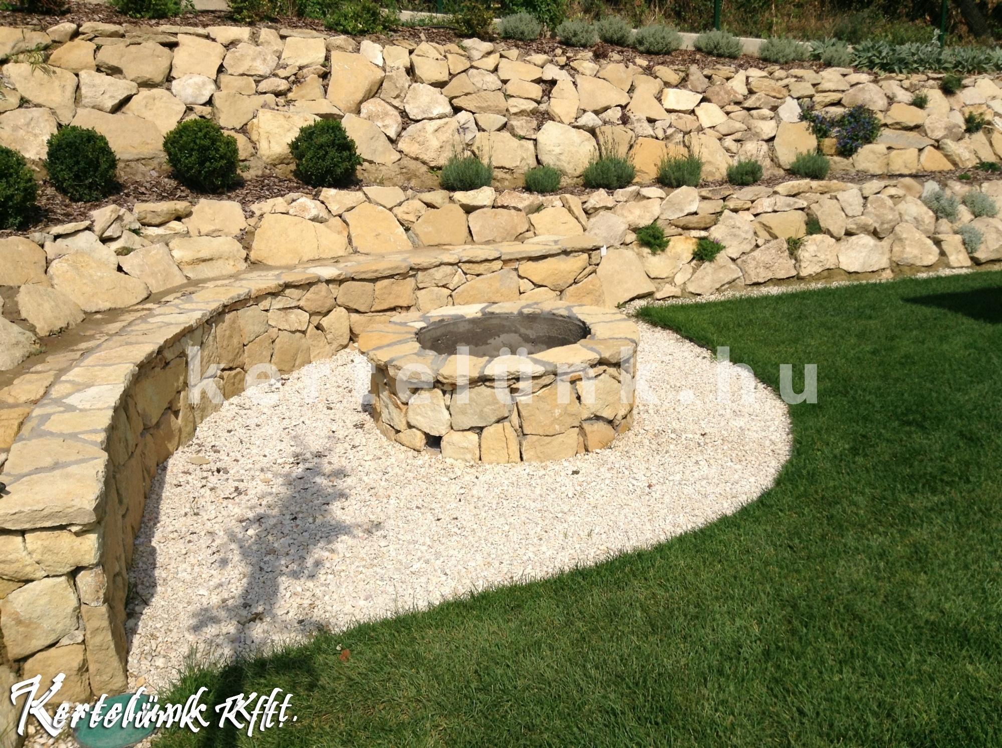 Kő támfal és kerti sütő egy kertben, mely a domboldoba épült.