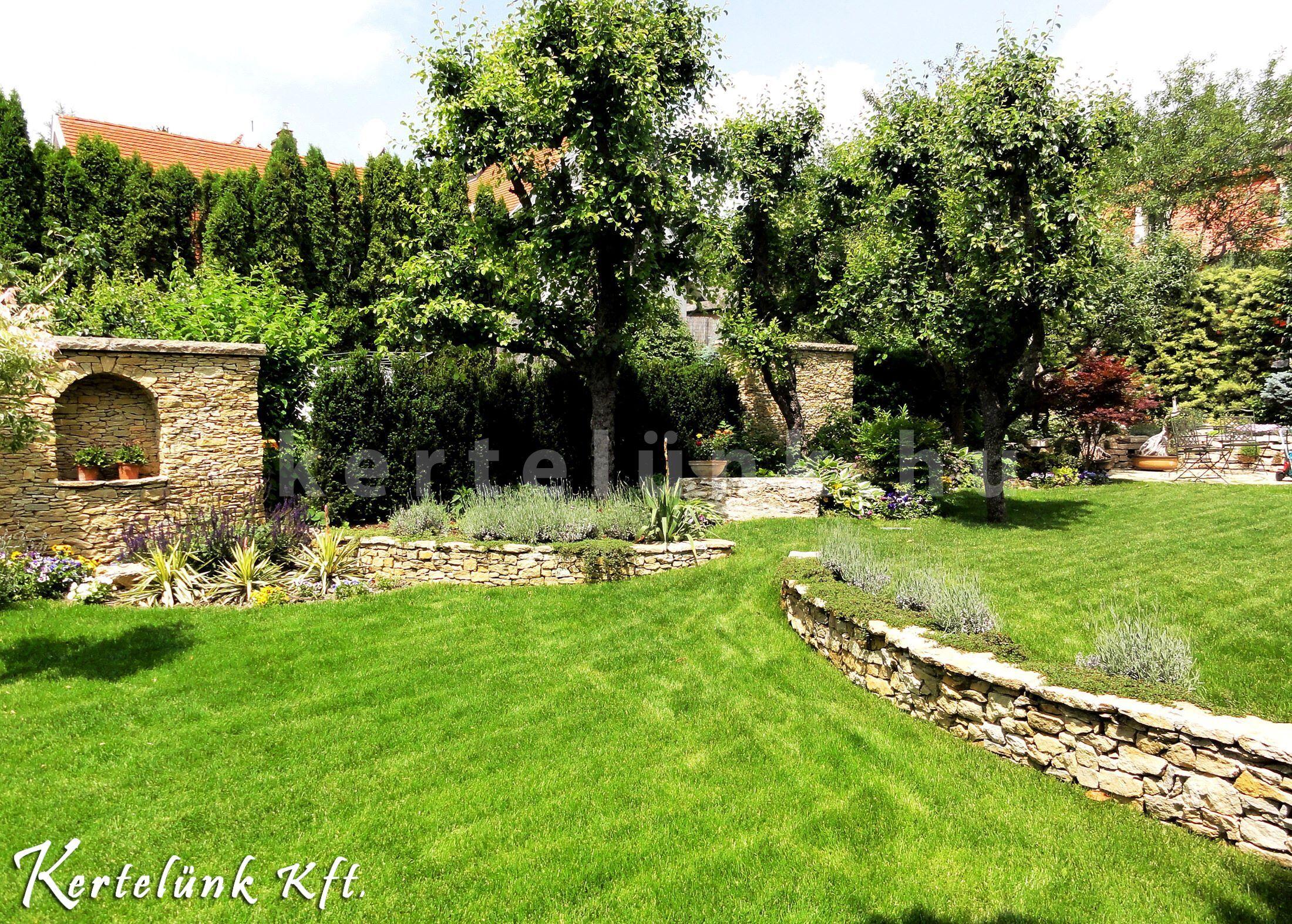 Üde zöld gyep, színes növények, mészkő támfalak.